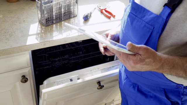 il lavoratore regola la lavastoviglie con tablet digitale - elettrodomestico attrezzatura domestica video stock e b–roll
