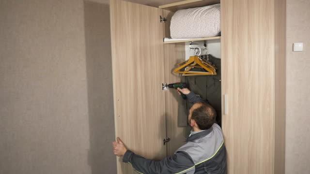 Travailleur s'ajuste les portes de l'armoire et installe le matériel, accessoires - Vidéo