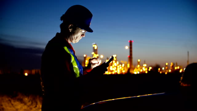 Video Worker at industrial plant working on a tablet.