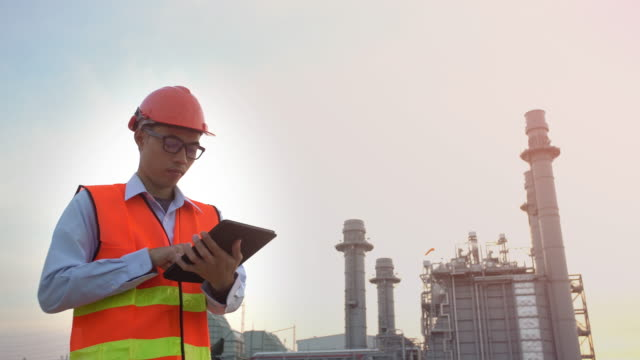 Worker at industrial plant working on a tablet. video