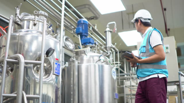 worker at industrial plant working on a tablet - fertilizzante video stock e b–roll