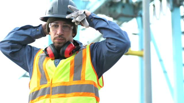 Worker at shipping port near crane, puts on hardhat A mixed race Hispanic and Caucasian man in his 30s working at a shipping port, wearing a reflective vest and safety goggles. He puts on his hardhat, looking at the camera, and then crosses his arms. In the background is a gantry crane for moving the cargo containers from the shipping vessels onto the port. work helmet stock videos & royalty-free footage