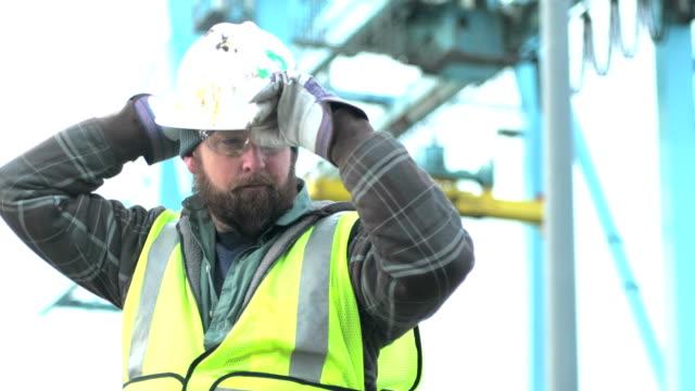 worker bei versand hafen in der nähe von kran, setzt auf bauarbeiterhelm - bauarbeiterhelm stock-videos und b-roll-filmmaterial