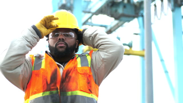 Worker at shipping port near crane, puts on hardhat A young African-American man in his 20s working at a shipping port, wearing a reflective vest and safety goggles. He puts on his hardhat, looking at the camera, and then crosses his arms. In the background is a gantry crane for moving the cargo containers from the shipping vessels onto the port. work helmet stock videos & royalty-free footage