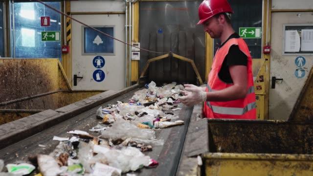 worker at waste disposal dump - odzyskiwanie i przetwarzanie surowców wtórnych filmów i materiałów b-roll