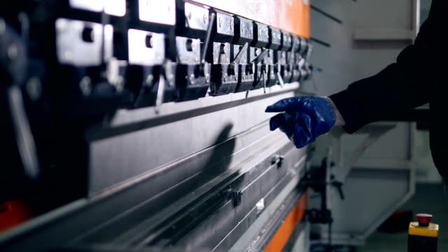 Worker bend metal sheet on a modern bending industrial machine at a factory. video