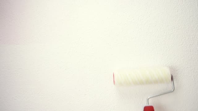 Worker bleach at work with the roller. Building. Caucasian house painter worker with roller works on a white wall. Construction industry. Footage. house painter stock videos & royalty-free footage