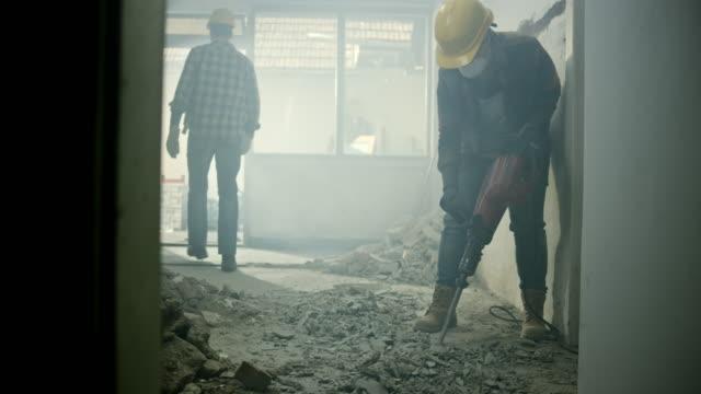 ds arbetare att bryta upp golvet i ett hus med en pneumatisk hammare - construction workwear floor bildbanksvideor och videomaterial från bakom kulisserna