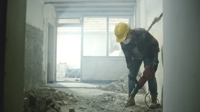 DS Worker chipping away the concrete floor in a house Wide dolly shot of a worker wearing a mask using a jackhammer to chip away the concrete floor in a house. Shot in Slovenia. work helmet stock videos & royalty-free footage