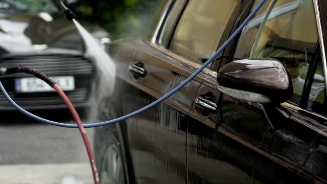 worker rengöring autos, sprutning vatten över fordonet, framgångsrik biltvätt företag - surf garage bildbanksvideor och videomaterial från bakom kulisserna