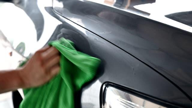 arbeiter reinigungsauto mit grünem mikrofasertuch mit kratzerentferner auf motorhaube - wachs epilation stock-videos und b-roll-filmmaterial