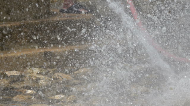 Worker cleaning the pool by using high pressure water spray