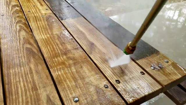 Worker cleans wooden outdoor table with pressure washer. video