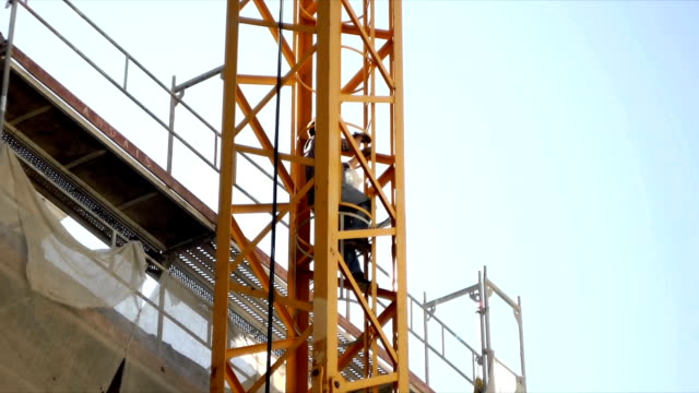 stockvideo's en b-roll-footage met worker climbs crane - ladder
