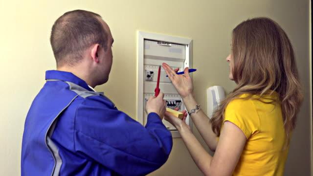 Arbeiter mit Frau Hausfrau mit Schutzschalter kommunizieren. FullHD – Video