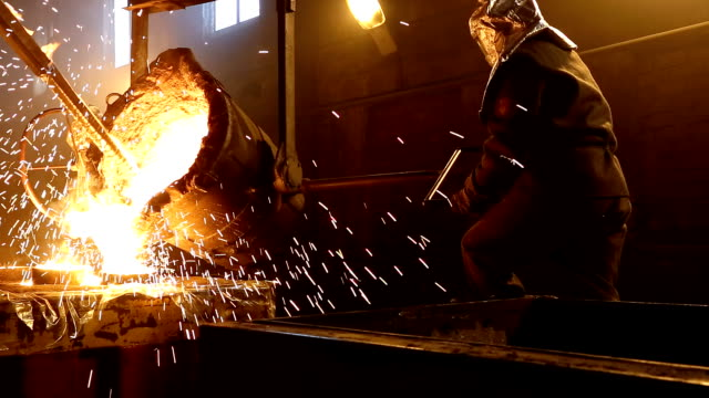 worker controlling metal melting in furnaces. - metallurgia video stock e b–roll