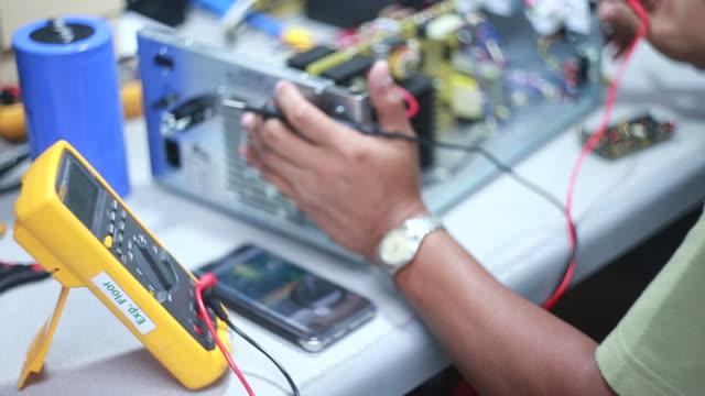 vídeos y material grabado en eventos de stock de trabajador de control eléctrica equipos en una fábrica con modernos equipos - electrónica