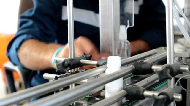 Worker controls the quality of products on the conveyor belt. Production line with small plastic bottles. Worker controls product quality. production line worker stock videos & royalty-free footage