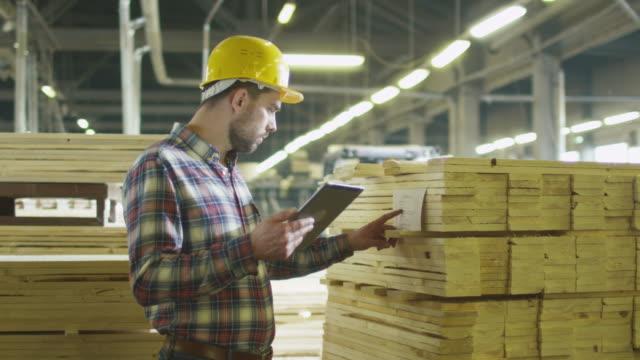 vídeos de stock e filmes b-roll de worker counts wood stock using a tablet computer at a lumber factory warehouse. - material de construção