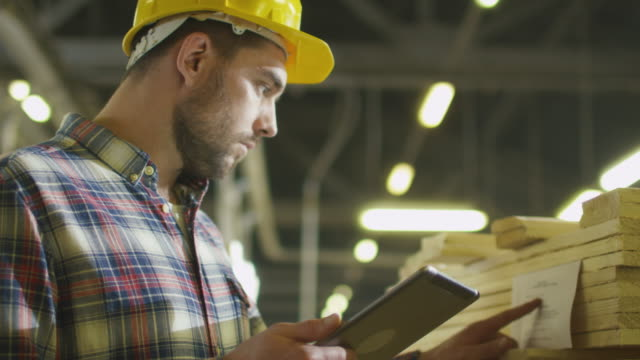 Worker counts wood stock using a tablet computer at a lumber factory warehouse. video
