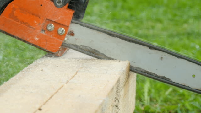 A worker cuts a wooden beam with a gasoline saw close-up video