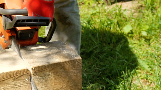 A worker cuts a wooden beam with a gasoline saw video