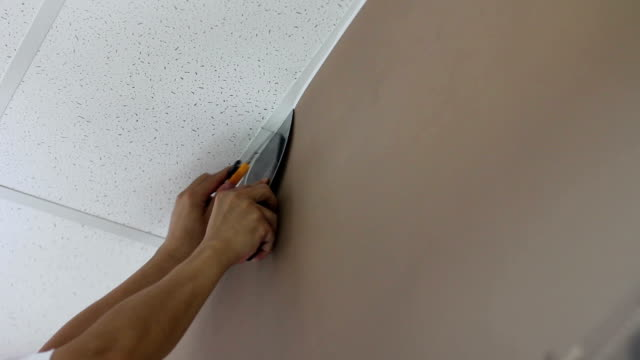 worker cuts extra wallpaper near the ceiling video