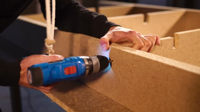 Worker drills wood in a studio Close up shot of carpenter drilling holes in a wood construction. He is using drilled holes to aim for new. handbook stock videos & royalty-free footage