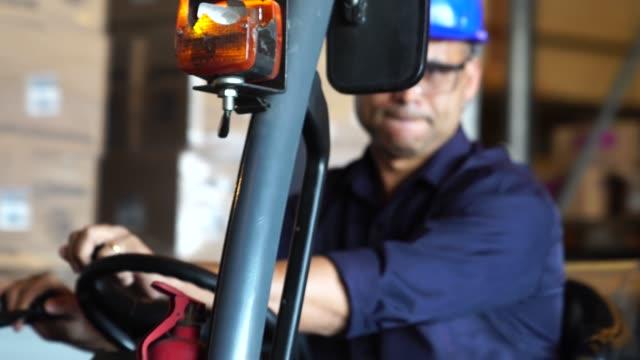 worker driving a forklift in warehouse - prodotti supermercato video stock e b–roll