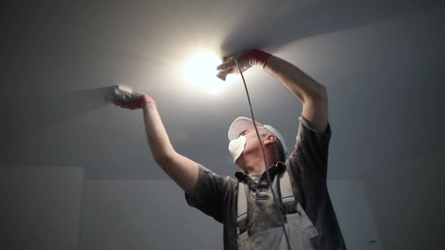 Worker finishing works, polishing a ceiling with sandpaper, with light bulb in other hand while standing on ladder