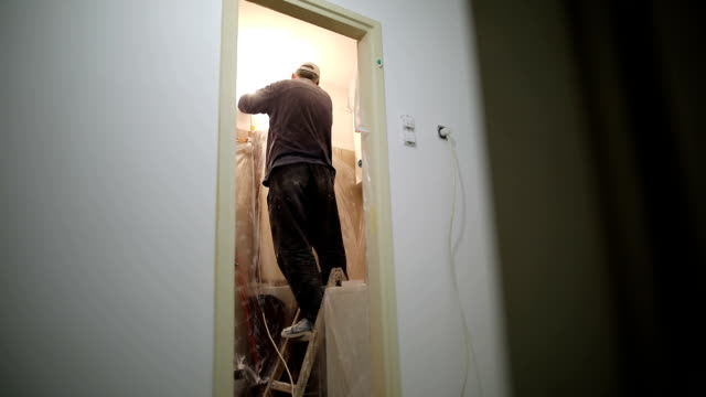 Worker finishing works, polishing a ceiling with sandpaper, with light bulb
