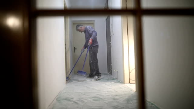 Worker finishing works,manual worker cleaning sawdust with broom after painting