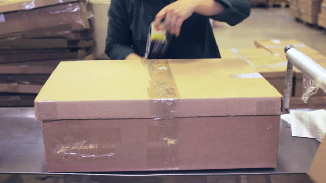 Worker glue tape on the box Employee packs products in a box in post structure stock videos & royalty-free footage