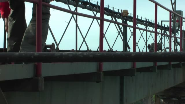 Worker goes on the metal construction. Worker goes on the metal construction. Worker is dressed in red jacket. railing stock videos & royalty-free footage