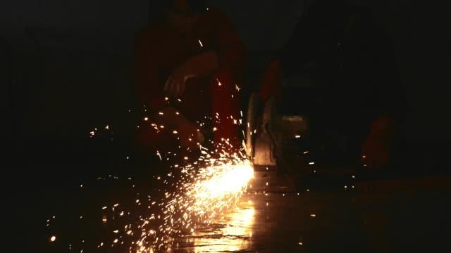 Worker grinding a sheet of metal