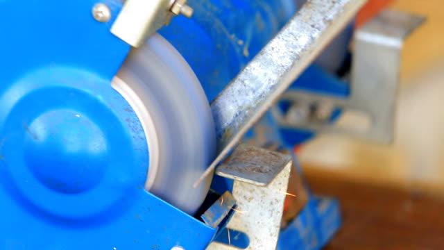 Worker grinding metal component on bench grinder video