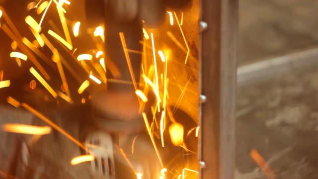 worker grinds metal video