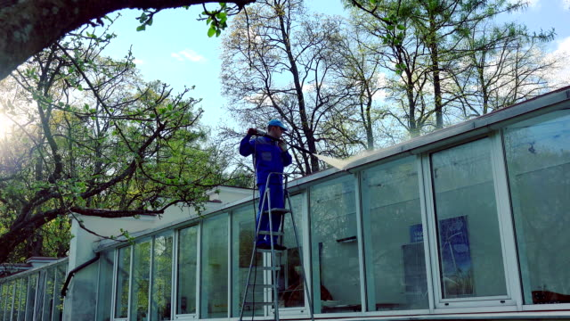 worker guy in uniform washing glass house with high pressure. video