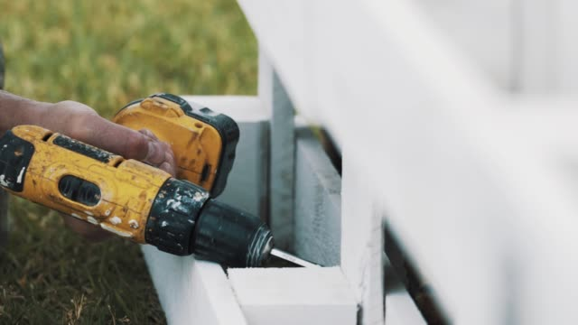 Worker hand use electric screwdriver to assamble wooden structure upon grass Carpenter worker hand use yellow electric screwdriver to assamble painted white wooden structure upon green grass lawn cordless phone stock videos & royalty-free footage