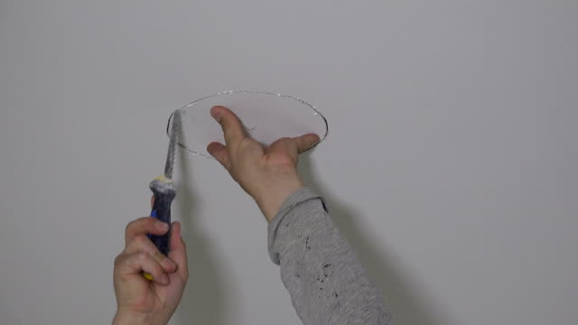 worker hand with handsaw cutting hole in drywall board ceiling - soffitto video stock e b–roll