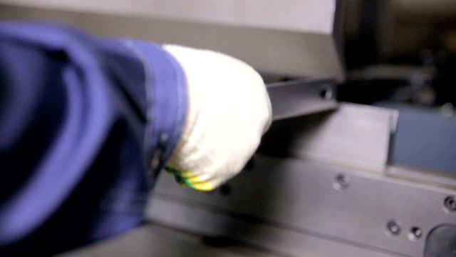 Worker hands bend metal sheet on a modern bending industrial machine at a factory video