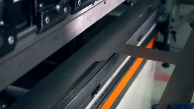 Worker hands bending metal sheet on a cnc bending machine. video