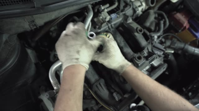 Worker hands changes spark plugs in car engine in auto service, close up video