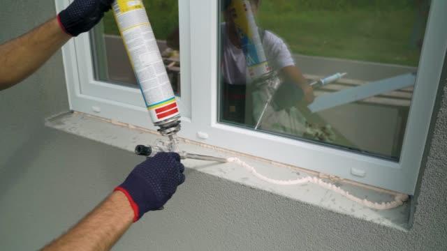 worker hands in protective gloves applying polyurethane construction foam on window sill closeup - poliuretano polimero video stock e b–roll