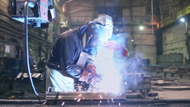 worker helping trainee using welding tool - apprendista video stock e b–roll