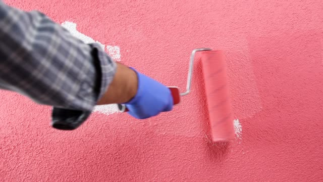Worker house painter painting the wall with pink paint. Building. Caucasian house painter worker in white overalls, with the roller painting the wall with painting pink. Construction industry. Footage. house painter stock videos & royalty-free footage