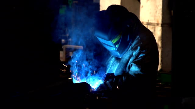 A worker in a protection mask welds some metal surface in a workshop of a plant video