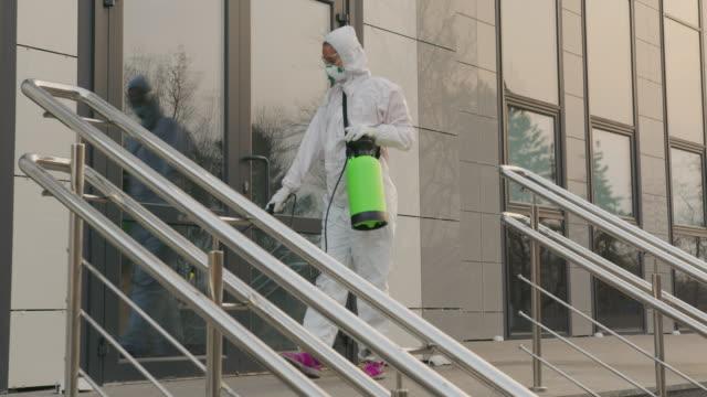 Arbeider in een beschermend kostuum desinfecteert oppervlakten van coronavirus. Antibacteriële sanitaire maatregelen bij quarantaine video