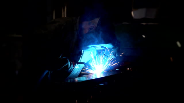 A worker in a uniform uses a welding machine, producing sparkling blue light video