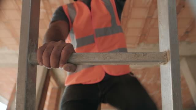 stockvideo's en b-roll-footage met worker in bouwplaats en gebouw nieuw huis - ladder